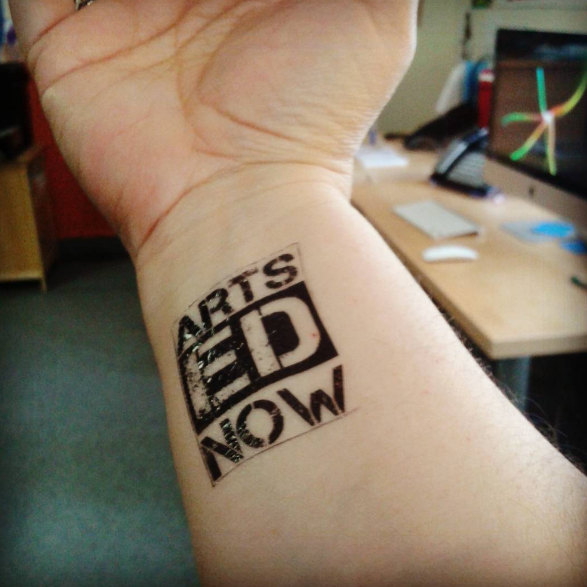 Arts Ed Now Tattoo on arm